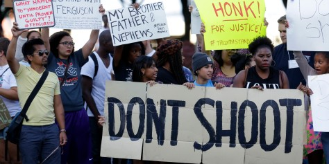 Protesters hold a sign that reads